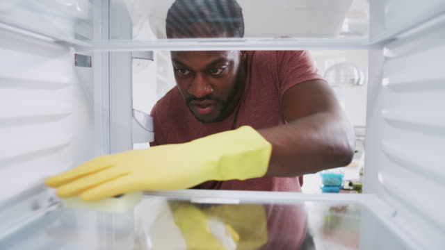View Looking Out From Inside Empty Refrigerator As Man Wearing Rubber Gloves Cleans Shelves View from inside fridge as man wearing rubber gloves cleans shelves - shot in slow motion fridge stock videos & royalty-free footage