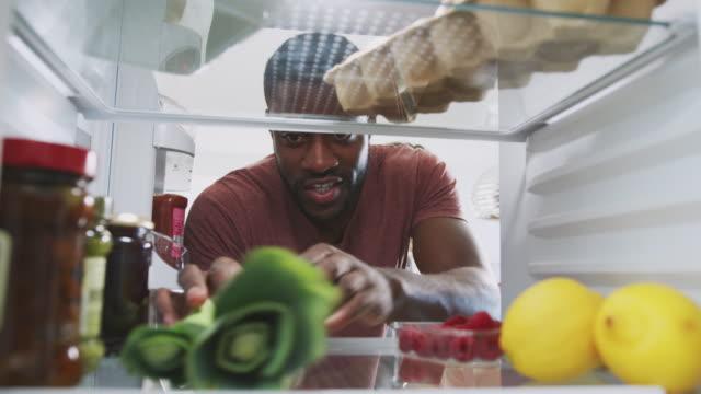 カップルがドアを開け、食べ物の買い物袋を開けると、冷蔵庫の中から外を見る - 荷物をとく点の映像素材/bロール