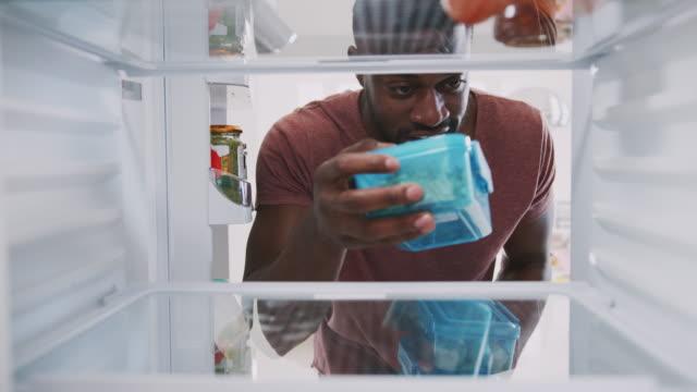 blick aus dem inneren des kühlschranks als mann stapelt gesunde lunchpakete in containern - portion stock-videos und b-roll-filmmaterial