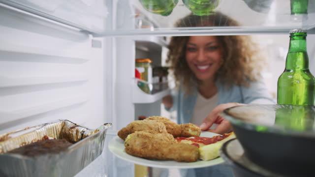 stockvideo's en b-roll-footage met uitzicht vanaf de binnenkant van de koelkast gevuld met afhaalmaaltijden eten als vrouw opent deur - dikke pizza close up