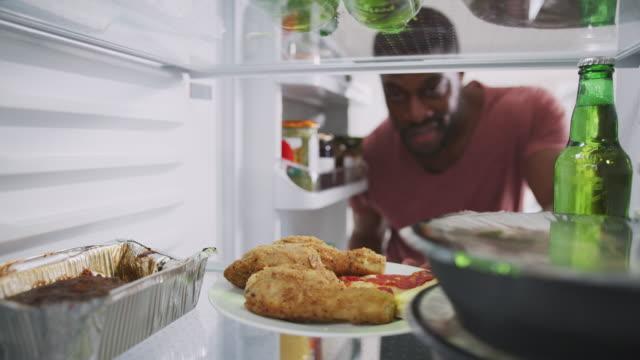 stockvideo's en b-roll-footage met uitzicht vanaf de binnenkant van de koelkast gevuld met afhaalmaaltijden eten als de mens opent deur - dikke pizza close up