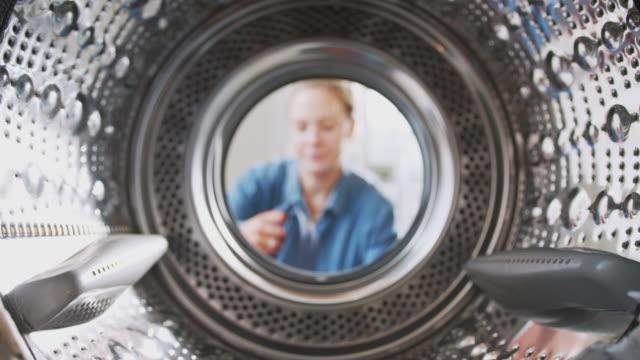 widok patrząc z wewnątrz pralka jak kobieta stawia w pralni obciążenia - pranie filmów i materiałów b-roll
