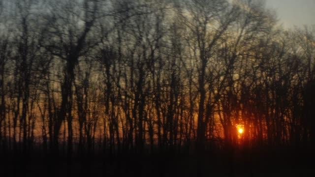 vidéos et rushes de vue d'un beau coucher de soleil depuis la fenêtre de la voiture ou le train - wagon