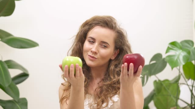 a view of a beautiful woman holding green and red apples and deciding which one to choose. she chooses green one and bites it - vegan stock videos and b-roll footage