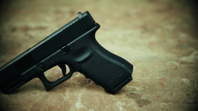 View of a black handgun on a concrete background Black handgun of soldiers from special troops on concrete gun stock videos & royalty-free footage