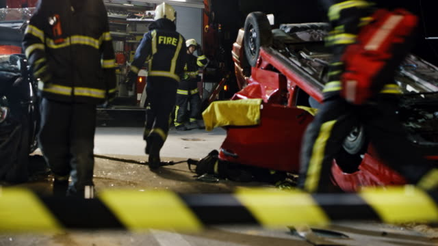 DS View of a car accident at night across the barricade tape Wide dolly shot of the view of a car accident across the barricade tape with firefighters rescuing the injured from the cars at night. Shot in Slovenia. car accident stock videos & royalty-free footage