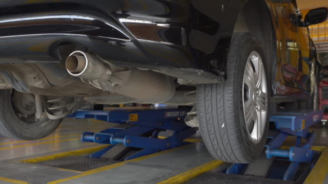 MS view of a car being raised on a hydraulic car lift at a servicing centre video