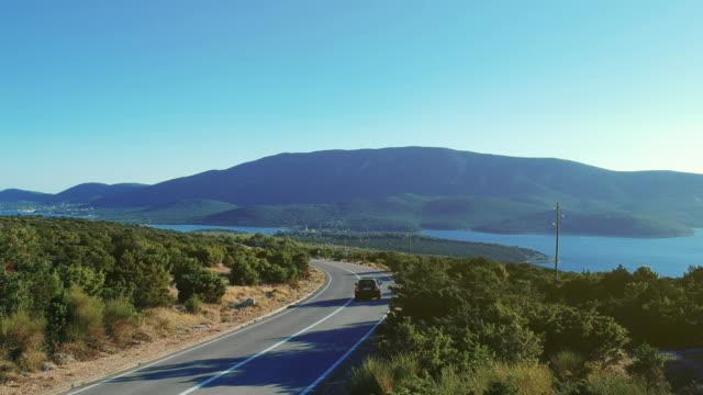vídeos de stock, filmes e b-roll de uma visão de um carro, dirigindo pela estrada de ilha no verão, com o mar mediterrâneo ao fundo. - veículo terrestre