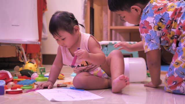 vy av ett barn ritning med kritor på papper eller göra läxor hemifrån - människorygg bildbanksvideor och videomaterial från bakom kulisserna