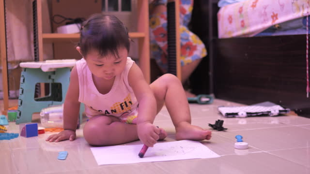 view of a child drawing with crayons on paper or doing homework from home - {{asset.href}} video stock e b–roll