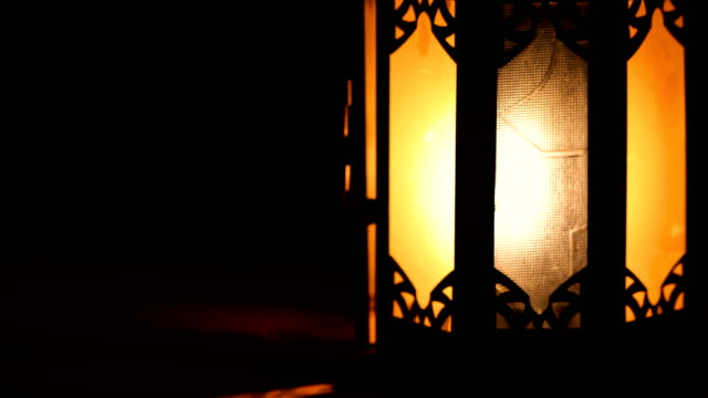 view of a classic arabian lantern, with an orange light because of the burning flame. everything is dark around the lantern. - lanterna attrezzatura per illuminazione video stock e b–roll