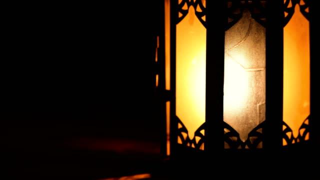 utsikt över en klassisk arabisk lykta, med ett orange ljus på grund av den brinnande flamman. allt är mörkt runt lyktan. - ramadan lykta bildbanksvideor och videomaterial från bakom kulisserna