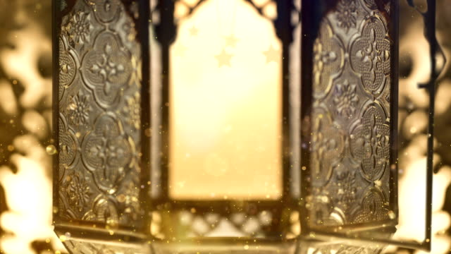 view of a golden lantern to celebrate ramadan kareem. a lots of lights in the video with animations. - фанус стоковые видео и кадры b-roll