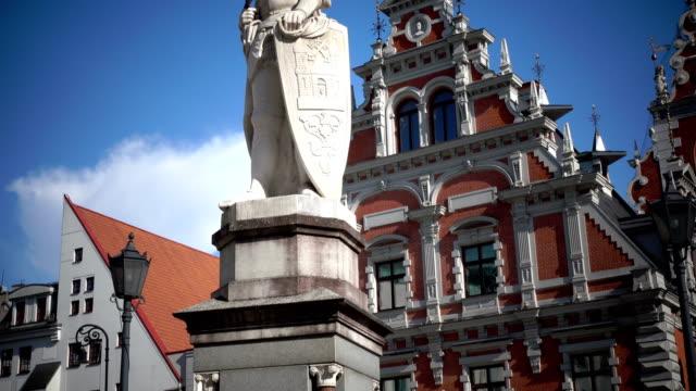 utsikt över ett monument till roland på rådhustorget mot bakgrund house of blackheads riga lettland - ancient white background bildbanksvideor och videomaterial från bakom kulisserna