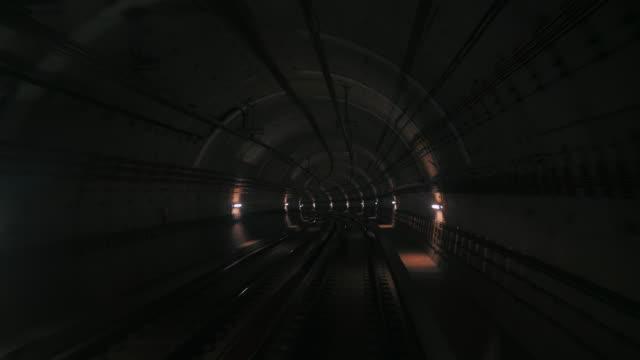 vídeos de stock, filmes e b-roll de vista de um túnel de metrô da frente de um trem em movimento. trem rápido subterrâneo, ganhando velocidade no túnel da cidade moderna. longa metragem de um metro em barcelona, seguindo sua rota. 4k - transporte ferroviário