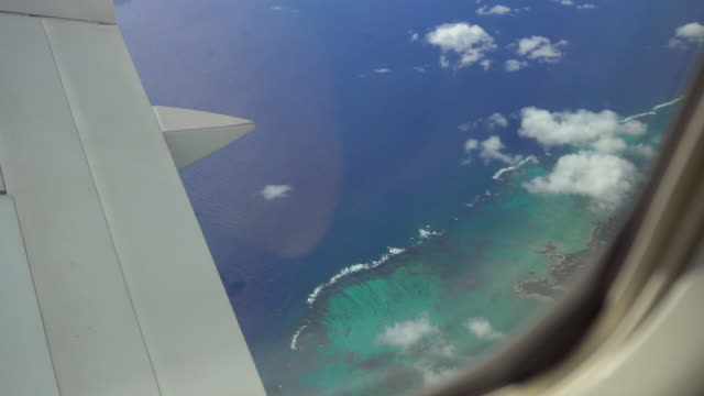 View of a tropical island from airplanes window during flight video
