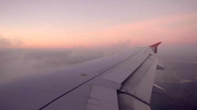 stockvideo's en b-roll-footage met weergave van een vleugel van een vliegtuig tijdens het vliegen bij zonsondergang - vliegveld vertrekhal
