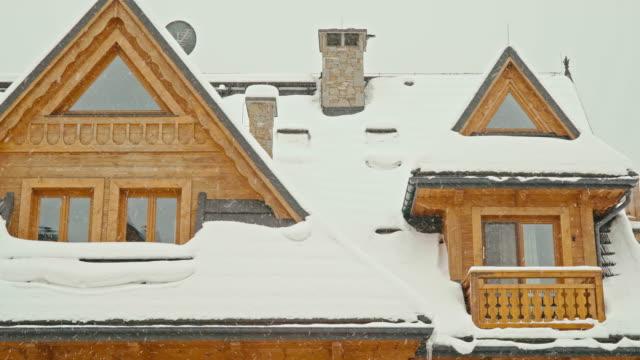 blick auf eine hölzerne highlander haus und schneeflocken - blockhütte stock-videos und b-roll-filmmaterial