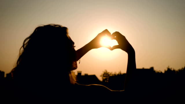 View of adorable woman silhouette holding sun in the field with a warm and vague background In summertime video