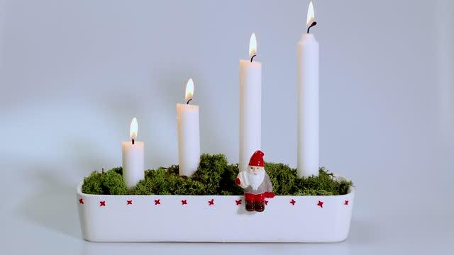 blick auf die adventskerze mit wenig figur des weihnachtsmannes und grünem moos verziert. - advent stock-videos und b-roll-filmmaterial