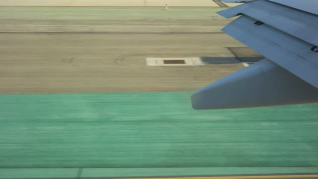 View of aircraft wing as plane moves on the runway video
