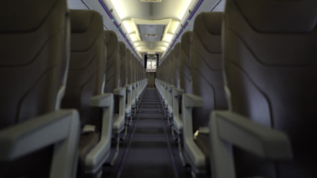 View of airplane seats through aisle View of airplane seats through aisle barren stock videos & royalty-free footage