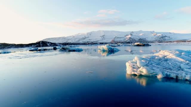 Vista de un increíble paisaje de témpanos blancos y un glaciar en Islandia. Sólo hay hielo blanco y nieve en el mar en el horizonte, bajo la puesta del sol. - vídeo