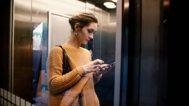 a view of attractive stressed busy caucasian woman riding up in transparent elevator using smartphone mobile office app - ascensore video stock e b–roll