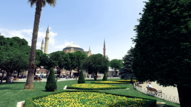 View of Aya Sofia through the Sultanahmet square with palm trees and flowers