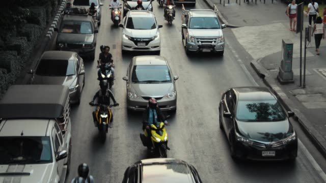 View of Bangkok traffic from above, sunset, cars and buses heading down road with bikes weaving in between.