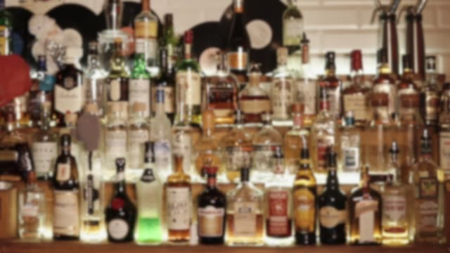 View of bar shelves with many of bottles with alcohol drinks, camera in movement Spirit drinks in bottles in a bar of night club. Camera is showing an assortment of alcoholic beverages bottle stock videos & royalty-free footage