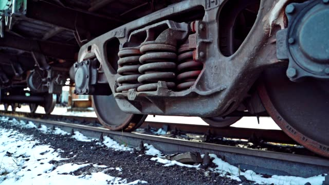 view of bottom to movement of powerful wheel mechanism of a freight car on the background of the ground with snow on the rail station. - parapetto barriera video stock e b–roll