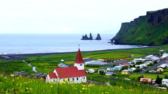 view of church on the hill of flowers in the village of vik - jesus christ filmów i materiałów b-roll