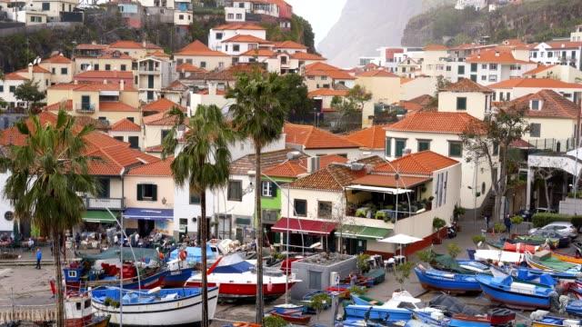 vídeos de stock e filmes b-roll de view of câmara de lobos in madeira with cape girão on the background and boats at the marina - ilha da madeira