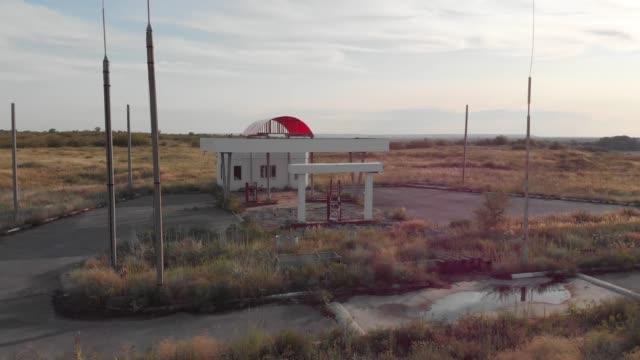 kış aylarında yolun yanındaki sahipsiz benzin istasyonunun görünümü. terk edilmiş benzin istasyonu ile yakıt belirtisi olmayan pompalar, ekonomik krizin kurbanı. tarihi rota 66. - i̇stasyon stok videoları ve detay görüntü çekimi