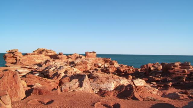 ws td view of dinosaur footprints with sea in background / broome, western australia, australia - utdöd bildbanksvideor och videomaterial från bakom kulisserna