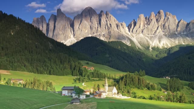 View of Dolomites at Santa Magdalena, Italy. Foothills are covered with green forest. Church and a few houses are in the foreground. Panoramic shot, 4K