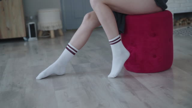 View of female legs with socks poses in room video