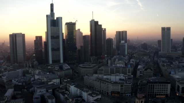 aerial: view of frankfurt am main, germany skyline with sunflair between skyscrapers in beautiful sunset sunlight in winter haze - francoforte sul meno video stock e b–roll