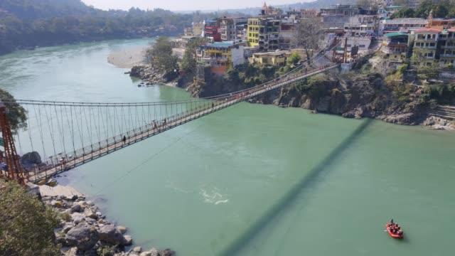 view of ganga river, lakshman jhula bridge in rishikesh. - ghat filmów i materiałów b-roll