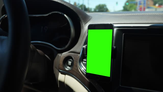 View of Green Screen Smartphone on Dashboard A handheld view of a driver's smartphone attached to a vent on the dashboard. Green screen with optional tracking points for advanced screen replacement. dashboard vehicle part stock videos & royalty-free footage
