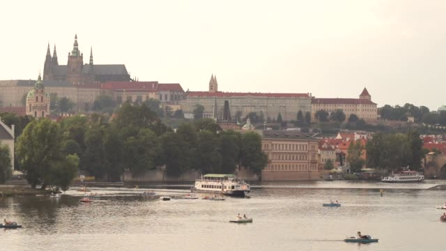A view of iconic Prague Castle and Vltava river in the evening. People enjoying the water activities, and river cruise passing by