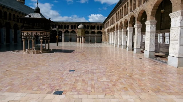 vídeos de stock e filmes b-roll de view of inside the courtyard of the umayyad mosque in syria. drone is flying from the inner courtyard of the mosque, where we see the building exterior inside the mosque, to the outside of the mosque. - síria