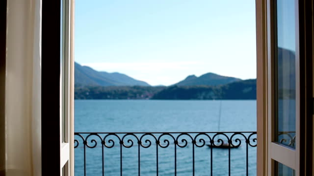 vídeos de stock e filmes b-roll de view of lago maggiore through closing window - lago maggiore
