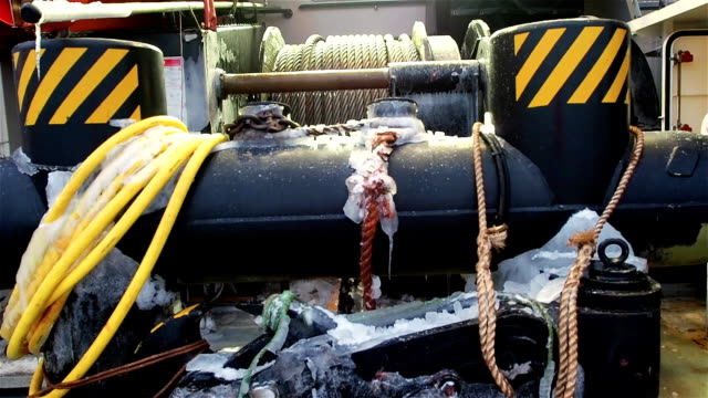 View of large bollard and windlass with cables on ship deck