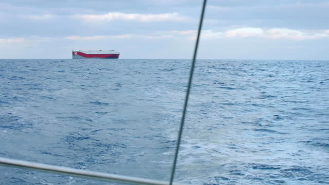 View of large ship from cockpit of yacht siling in ocean video