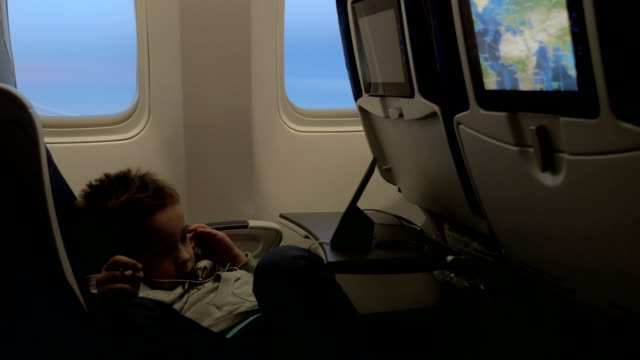 view of little boy watching films in headset in the aircraft lying on the seat against airplane window - sedili aereo video stock e b–roll