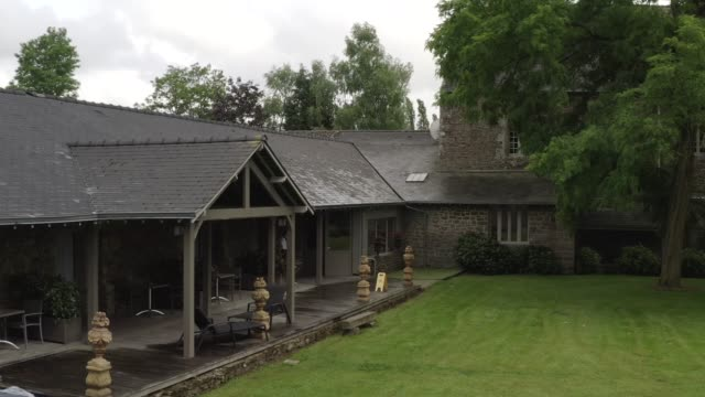 View of luxury grey stone house and terrace near the garden and large old tree in summer day against cloudy sky. Action. Beautiful view of countryside cottage video