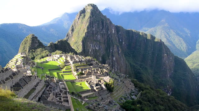 view of machu picchu and the mountains that surround the city - объект мирового наследия юнеско стоковые видео и кадры b-roll
