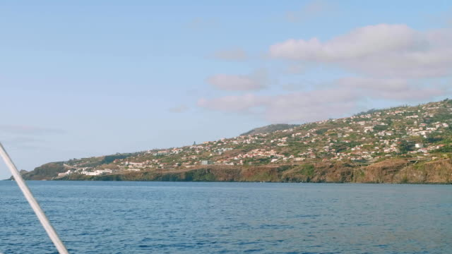 View of Madeira island with its cliffy shore, white houses and buildings, roads and trestles. View from sailing yacht video